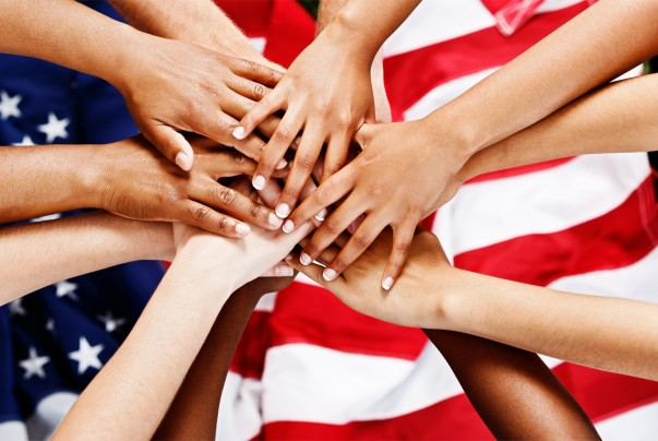 A pile of mixed hands, in loyal co-operation, on top of the American flag. Some patriotic citizens pledging their allegiance and unity.